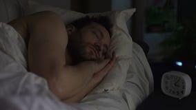 Homme barbu dormant sur le canapé-lit, horloge se tenant sur la table de nuit, repos de fin de nuit banque de vidéos
