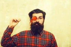 Homme barbu drôle tenant le coeur rouge sur le bâton avant oeil photos stock