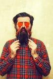 Homme barbu drôle tenant les coeurs rouges sur des bâtons avant des yeux photos stock