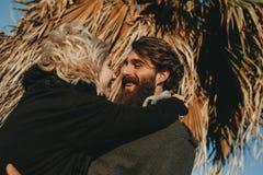Homme barbu embrassant son amie au coucher du soleil tandis que rires et regard à ses yeux Photo stock