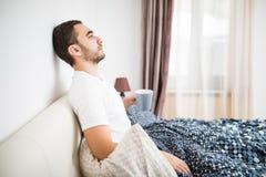 Homme barbu en café potable de matin de lit dans la lumière de lever de soleil à la maison image stock