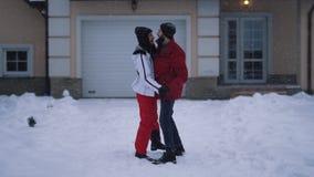 Homme barbu et danse de sourire de femme dans l'arrière-cour d'hiver Les couples heureux ont un amusement ensemble La neige tombe banque de vidéos
