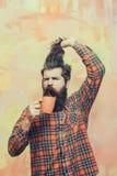Homme barbu fâché tenant les cheveux de frange et la tasse orange Photo libre de droits
