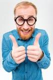 Homme barbu gai drôle en verres ronds montrant des pouces  Images stock