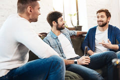 Homme barbu gai racontant à ses amis une histoire Image libre de droits