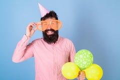 Homme barbu heureux en verres énormes posant avec les ballons lumineux, concept d'amusement Comédien avec les invités amusants de photo stock
