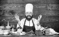Homme barbu heureux faisant cuire dans la cuisine Suivre un r?gime avec l'aliment biologique Produit-l?gumes frais de vegetables  photographie stock libre de droits