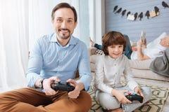Homme barbu heureux jouant des jeux vidéo avec son fils Photos libres de droits