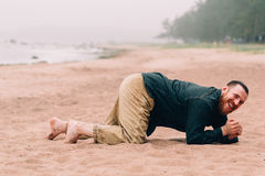 Homme barbu heureux rampant sur tous les fours la plage image libre de droits