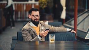 Homme barbu heureux regardant l'écran et le sourire du ` s de téléphone portable clips vidéos