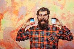 Homme barbu heureux tenant deux pots cosmétiques images stock