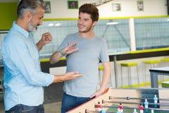 Homme barbu jouant le football de table avec le jeune travailleur Image libre de droits
