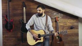 Homme barbu jouant un mouvement lent de guitare acoustique banque de vidéos