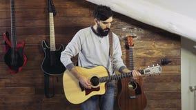 Homme barbu jouant un mouvement lent de guitare acoustique clips vidéos
