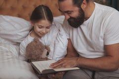 Homme barbu mûr dépendant à la maison de sa petite fille image libre de droits