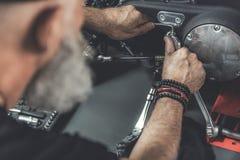 Homme barbu mûr faisant la rénovation de la motocyclette Photo stock
