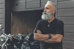 Homme barbu mûr réfléchi plaçant près du garage Image stock