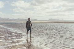 Homme barbu musculaire bel se tenant sur le bord de mer au lever de soleil Portrait latéral du jeune fonctionnement barbu sain d' photos libres de droits