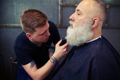Homme barbu obtenant sa barbe rasée Photographie stock libre de droits
