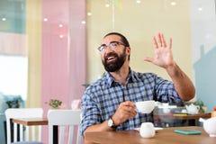 Homme barbu ondulant sa main tout en voyant le vieux ami en café image libre de droits