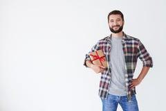 Homme barbu positif tenant la boîte actuelle sous son bras Photographie stock