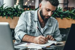 Homme barbu sérieux de hippie s'asseyant dans le bureau, faisant des notes dans le carnet, fonctionnant L'entrepreneur analyse l' photo libre de droits