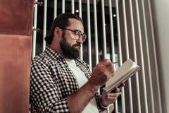 Homme barbu sérieux regardant dans son carnet photographie stock libre de droits