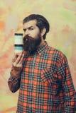Homme barbu sérieux tenant deux pots cosmétiques image libre de droits
