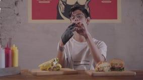 Homme barbu s'asseyant à la table devant l'hamburger appétissant et shawarma se préparant à la consommation Le type mettant dessu banque de vidéos