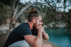 Homme barbu s'asseyant avec son amie au milieu de la nature Photo stock