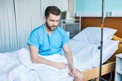 Homme barbu s'asseyant sur le lit d'hôpital avec le compteur de baisse photo libre de droits