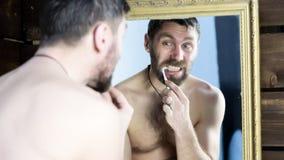 Homme barbu se brossant les dents devant le miroir dans la salle de bains Image libre de droits