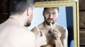 Homme barbu se brossant les dents devant le miroir dans la salle de bains Images libres de droits