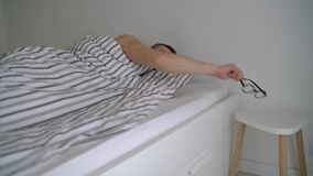 Homme barbu se réveillant dans le lit sous la couverture, souriant, mettant ses lunettes dessus et claquer banque de vidéos