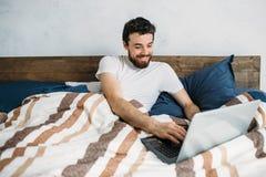 Homme barbu se situant dans le lit de matin avec l'ordinateur portable Photos libres de droits