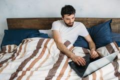 Homme barbu se situant dans le lit de matin avec l'ordinateur portable photographie stock