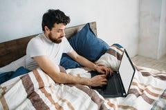 Homme barbu se situant dans le lit de matin avec l'ordinateur portable Photo libre de droits