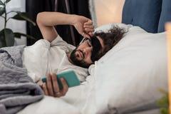 Homme barbu somnolent tenant son instrument mobile photos libres de droits