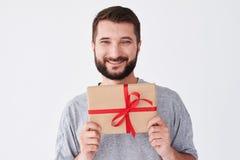 Homme barbu souriant dans le T-shirt gris tenant la boîte actuelle Photos libres de droits