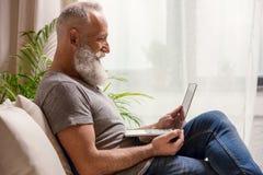 Homme barbu souriant et regardant l'ordinateur portable tout en se reposant sur le sofa à la maison Photos libres de droits