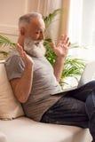 Homme barbu supérieur à l'aide de l'ordinateur portable tout en se reposant sur le sofa à la maison Images libres de droits