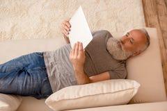 Homme barbu supérieur à l'aide du comprimé numérique et se trouvant sur le sofa à la maison Photo stock