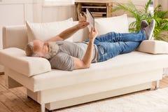Homme barbu supérieur à l'aide du comprimé numérique et se trouvant sur le sofa image stock