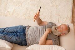 Homme barbu supérieur étonné à l'aide du comprimé numérique tout en se trouvant sur le sofa Photo stock