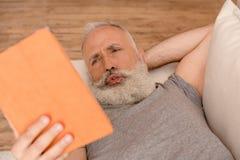 Homme barbu supérieur confus à l'aide du comprimé numérique tout en se trouvant sur le sofa Photographie stock