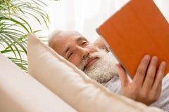 Homme barbu supérieur heureux à l'aide du comprimé numérique et se trouvant sur le sofa Photographie stock