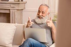 Homme barbu supérieur regardant l'ordinateur portable et se dirigeant tout en se reposant sur le sofa à la maison Image stock