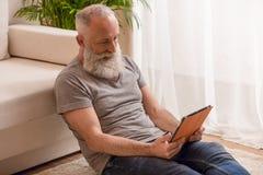 Homme barbu supérieur souriant et à l'aide du comprimé numérique et s'asseyant sur le plancher Photographie stock