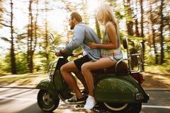 Homme barbu sur le scooter avec l'amie dehors Photos libres de droits