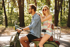 Homme barbu sur le scooter avec l'amie dehors Photographie stock